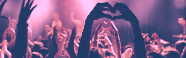 Picture of somebody forming a heart in a dancing crowd